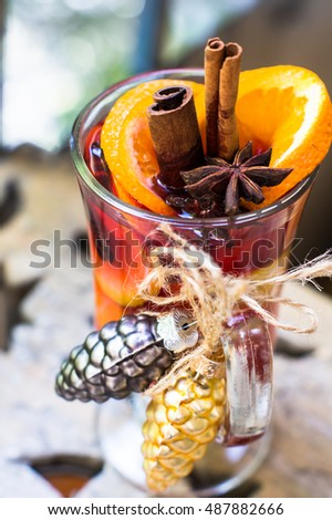 Mulled wine in a glass and christmas time decorations on rustic wooden table