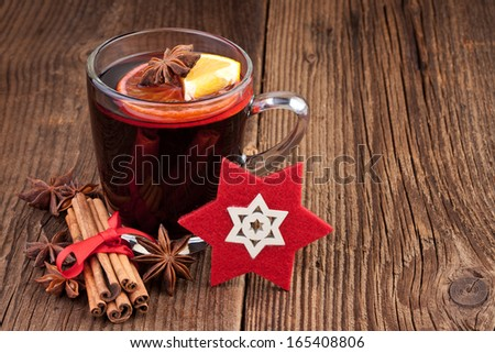 Mulled wine in a glass on old wooden background - stock photo