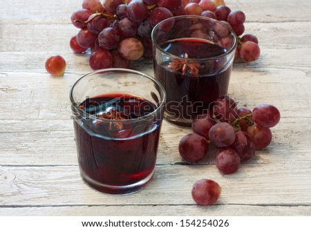 Mulled wine in glasses and red grapes over wood background - stock photo
