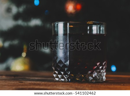Mulled wine on wooden table over christmas tree background. Christmas hot red mulled wine in winter.