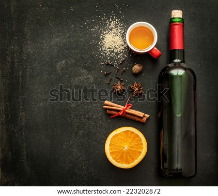 Mulled wine recipe ingredients on black chalkboard with text space - christmas or winter warming drink. Bottle of wine, honey, orange, cinnamon sticks, anise, nutmeg, cloves and sugar from above. - stock photo