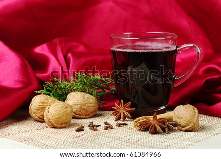 Mulled wine with cinnamon, star anise, walnuts, cloves and a branch of evergreen on mat with red fabric as background (Selective Focus) - stock photo