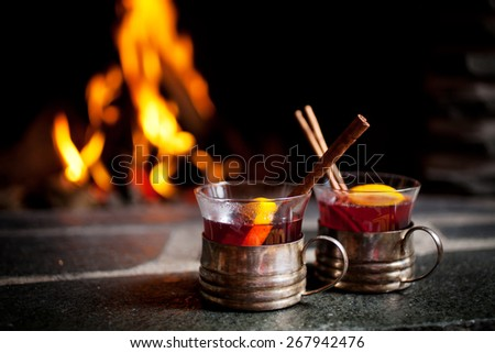 Mulled wine with cinnamon stick by the fireplace - stock photo