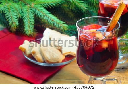 Mulled wine with cinnamon sticks in glass and christmas cookies in plate on the wooden table with christmas tree branch on background