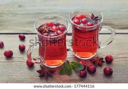 Mulled wine with fresh cranberry and anise on wooden background - stock photo