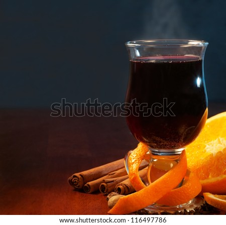 Mulled wine with orange and spices on dark background with copy space - stock photo
