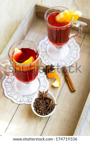 mulled wine with spices, sweets and orange on a wooden table