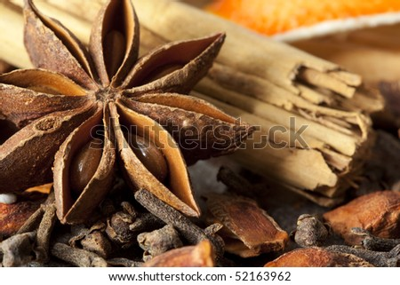 Mulling spices, including star anise, cinnamon sticks, cloves, and dried orange.
