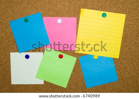 Multi-color blank post it notes pinned on cork board