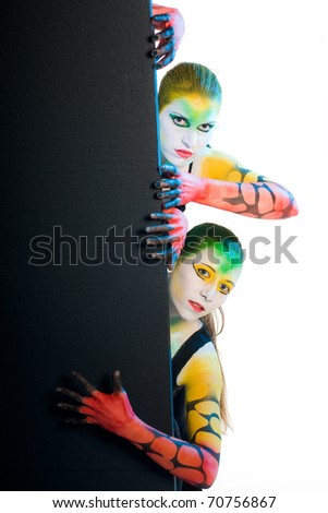 multi color bodypainting with red yellow green hidden behind black wall - stock photo