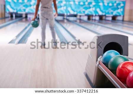 Multi-color bowling balls on background of guy standing in alley