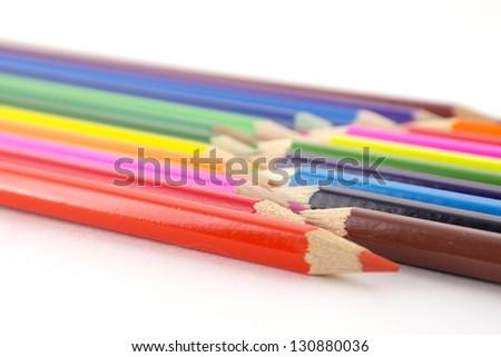 Multi color pencils over white. Shallow DOF. - stock photo