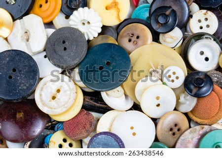 Multi color sewing buttons laid flat and piled on top of each other to form a vintage abstract background. - stock photo