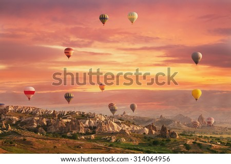 Multi-colored air shata fly over rocks in Cappadocia at sunrise - stock photo
