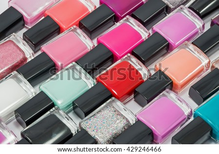 Multi-colored bottles with nail polish laid out on a white background - stock photo