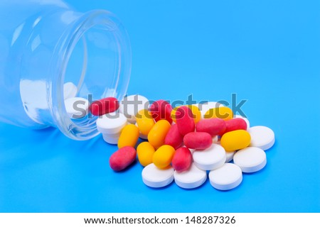 Multi colored capsules spilling from a prescription medicine bottle - stock photo