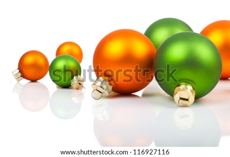 Multi-colored Christmas ornaments - orange and  green, on a white background with copy space - stock photo