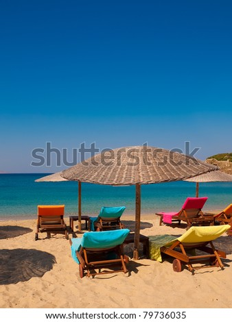 multi-colored deck chairs on the beaches of Greece.