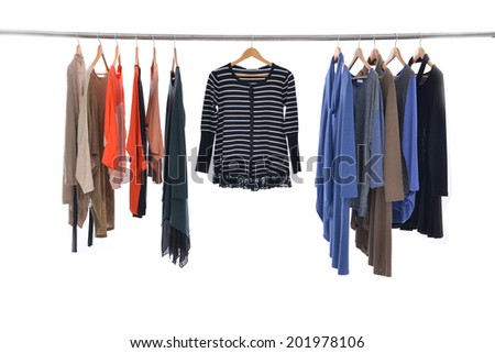 Multi colored female shirts with sundress on hangers against a white background  - stock photo