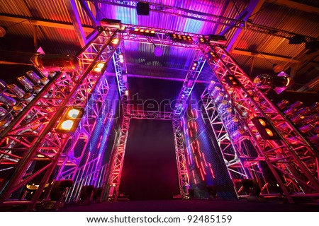 Multi-colored illuminated way to boxing ring inside fight club; many lights - stock photo