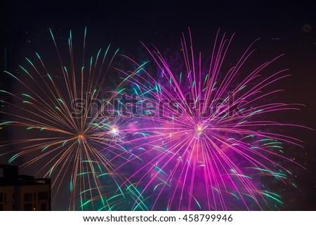 Multi colored magenta fireworks burst above buildings - stock photo