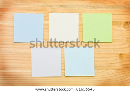 Multi-colored notes on a wooden background - stock photo