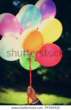 Multi colored party balloons are ready to fly away to the sky, but groom is holding them in hand. - stock photo