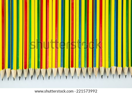 Multi colored pencils in a row on a white background - stock photo