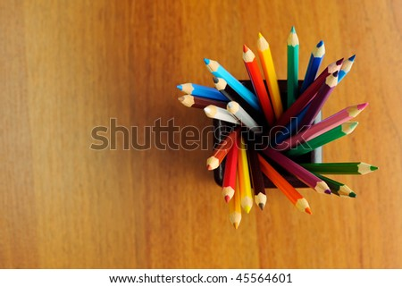 Multi-colored pencils in wood cup on wooden table background - view above - stock photo