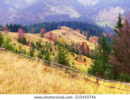 Multi Colored retro lighting autumn Carpathians panorama with a wooden fence in the foreground. - stock photo