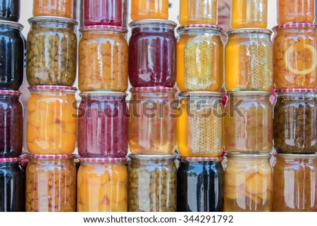 Multi-colored rows of glass jars with fruits, honey