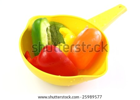 Multi-colored sweet bell pepper halves in a yellow strainer.