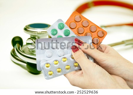 Multi-colored tablets in hands of doctors on a red stethoscope - stock photo