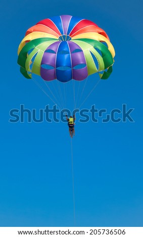 Multi coloured parachute over the blue sky - stock photo