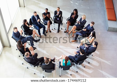 Multi-Cultural Office Staff Applauding During Meeting - stock photo