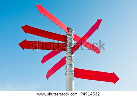 Multi-directional empty sign with many red arrows on post - stock photo