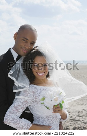 Multi-ethnic bride and groom hugging - stock photo