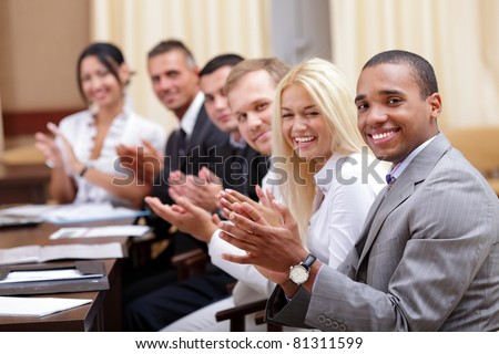 Multi ethnic business group greets you with clapping and smiling - stock photo