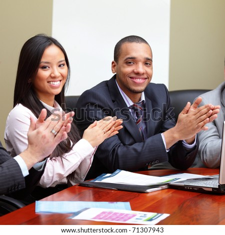 Multi ethnic business group greets you with clapping and smiling. Focus on woman - stock photo