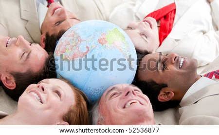 Multi-ethnic business people lying on the floor around a terrestrial globe - stock photo