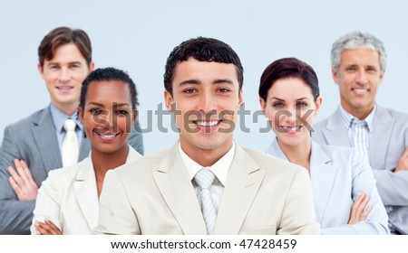 Multi-ethnic business people standing with folded arms in front of the camera