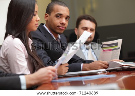 Multi ethnic business team at a meeting. Focus on african-american young man - stock photo
