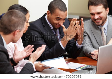 Multi ethnic business team at a meeting. Interacting. Focus on african-american man - stock photo