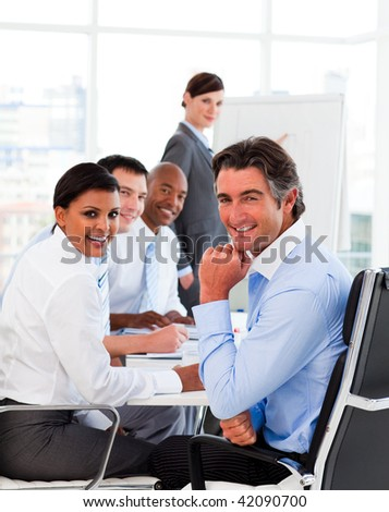 Multi-ethnic business team at a meeting smiling at the camera - stock photo