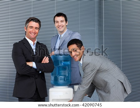 Multi-ethnic business team at water cooler in the office - stock photo
