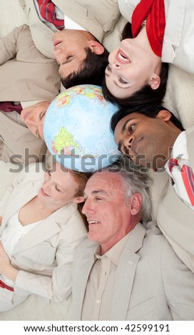Multi-ethnic business team lying on the floor around a terrestrial globe. Business concept. - stock photo
