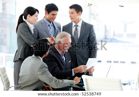 Multi-ethnic business team studying a document in a meeting - stock photo