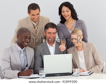 Multi-ethnic business team working with a laptop in office together