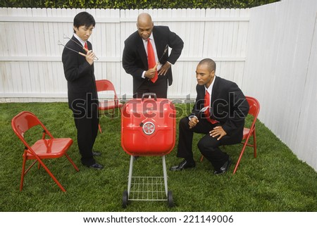 Multi-ethnic businessmen looking at barbeque - stock photo