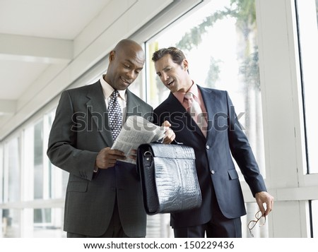 Multi ethnic businessmen reading newspaper together in office - stock photo